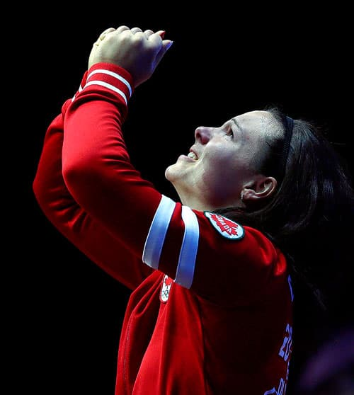 Female Canadian Olympic athlete holding medal up in the air with both hands.