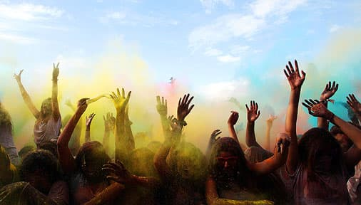 hands waving through colour clouds in a concert audience