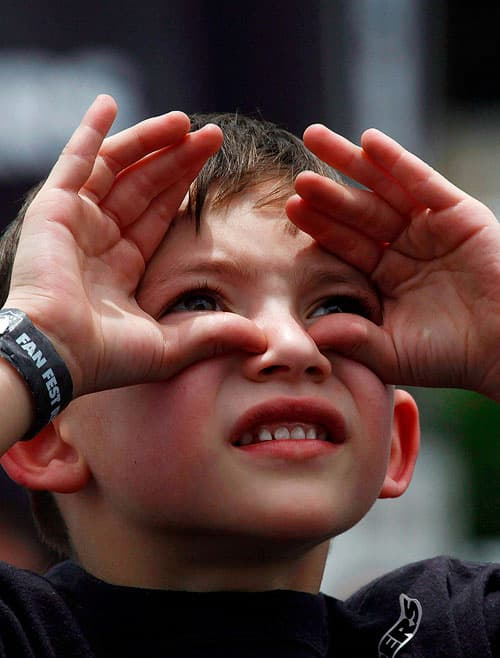custom content - A boy looking up and shielding his eyes from the sun.