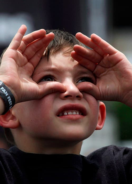 A boy looking up and shielding his eyes from the sun.