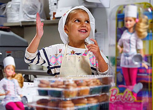 Little girl dressed like a baker surrounded by Barbie dolls dressed as a baker.