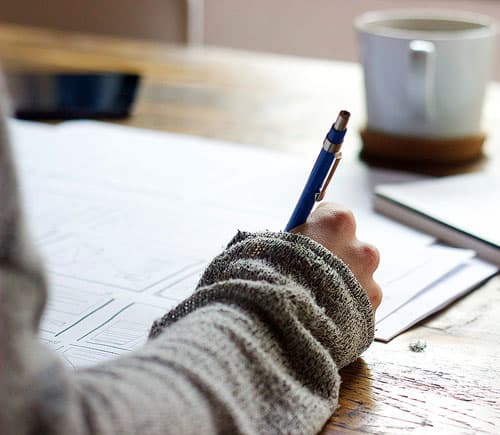 A person writing at a desk.