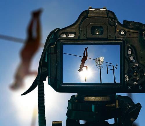 A professional camera on a tripod captures a high jump performance