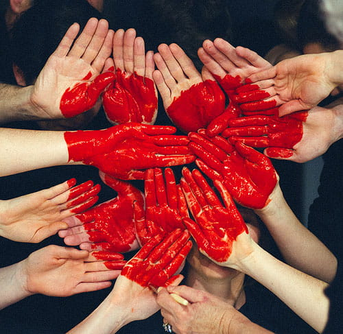 14 red painted hands grouped together to display a heart.