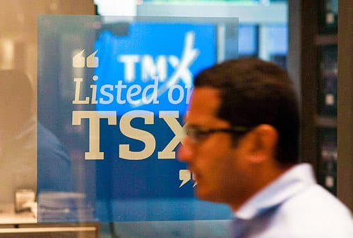 "financial trader in front of a sign that says ""listed on T S X"""