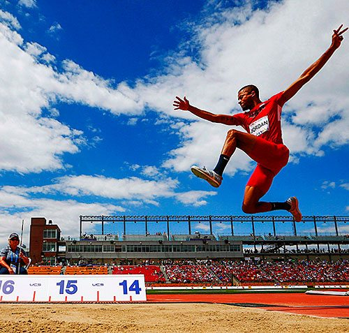 Track and Field athlete pictured mid-air during long jump event.