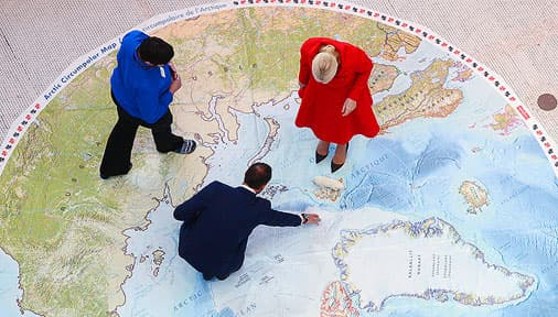 people walking over a map showing the regions of the world