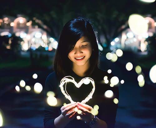 Young woman playing with lights shaped like a heart.