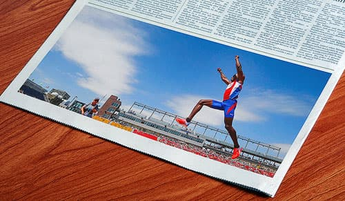 Newspaper image of a track and field athlete jumping in mid-air in an outdoor stadium.