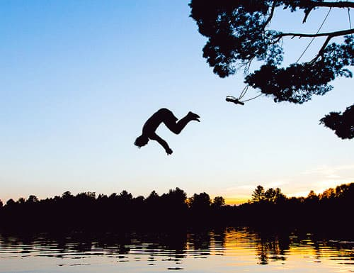 Silhouette of someone in midair as they swing from a tree into a lake.
