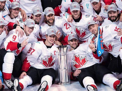 Canadian Men's Olympic Hockey team posing with trophy.