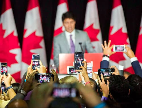 Audience members take a pictures with smartphones as Prime Minister Justin Trudeau speaks at an event at Paramount Fine Foods in Mississauga.