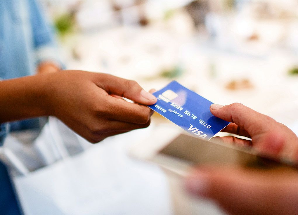A person handing a Visa card to another person.
