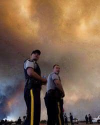 Police officers direct traffic under a cloud of smoke from a wildfire in Fort McMurray.