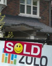 "Real Estate sign saying ""Sold Out"" in front of a house."