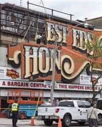 Workers remove part of the iconic sign from the shuttered Honest Eds department store in Toronto.