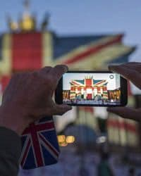 Picture of someone holding a cell phone taking a picture of the union jack flag