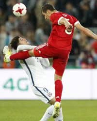 Two soccer players colliding as they try to get the ball.