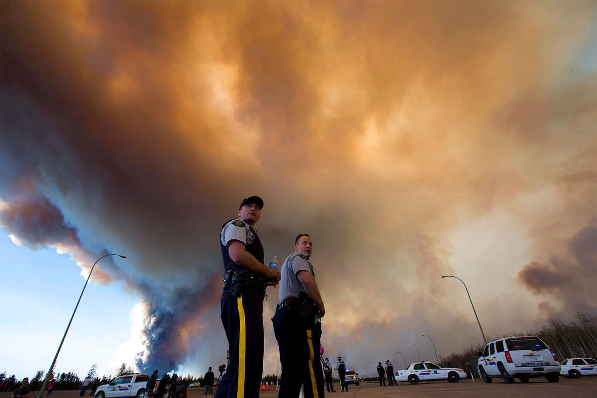 Police officers direct traffic under a cloud of smoke from a wildfire in Fort McMurray, Alberta.