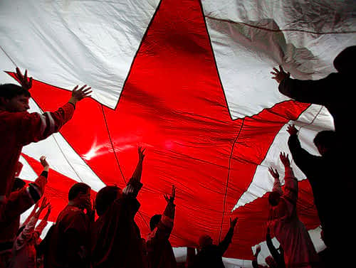 Group of people standing under a large parachute with a red maple leaf emblazoned on it.
