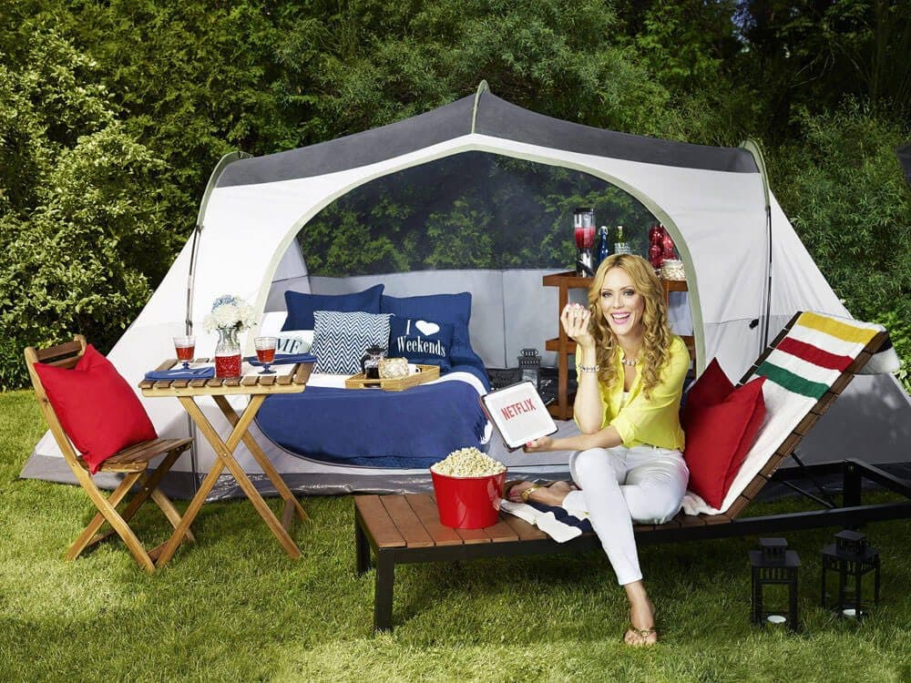 Woman sitting in a camping display designed by The Bay.