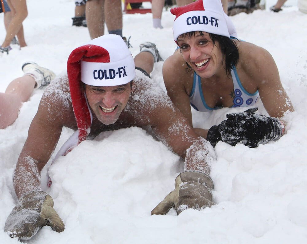 Corporate: Two revellers smile for the cameras at the Quebec Winter Carnival (Carnaval de Quebec) in Quebec City, Saturday, February 11, 2012.  Despite -11 degree temperatures, more than 50 participants in bathing suits frolicked in the snow in the 26th annual Snow Bath (Bain de Neige). The Canadian Press Images PHOTO/Afexa Life Sciences Inc.