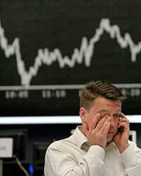 Man standing in front of a stock market screen.
