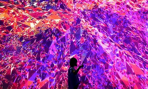 A woman standing in front of an art display.