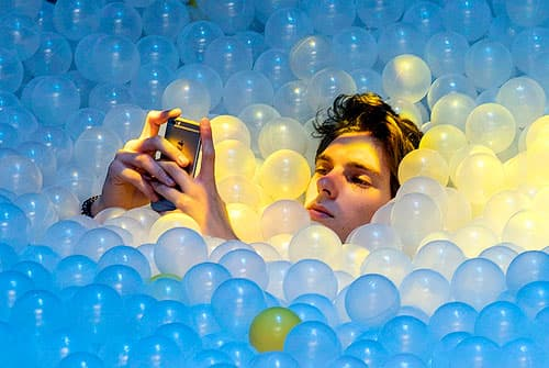 Man taking a selfie in a pool of balls.