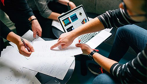 Three people gathered around a laptop and papers planning.