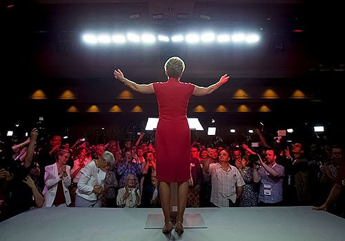 A picture of Kathleen Wynne from behind, standing on a stage, speaking to a group of people.