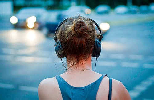 Picture of a woman from behind wearing large headphones.