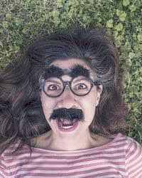 Girl wearing Groucho Marx glasses with fake eyebrows and mustache.