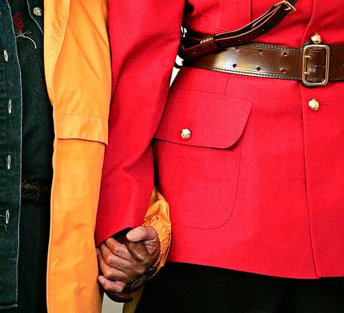 A Royal Canadian Mounted Police Officer holding hands with a Canadian citizen.