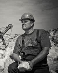 A man wearing a hard hat, sitting in a rock quarry.