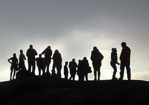 Silhouette of a group of people standing on a hill.