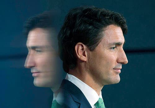 Headshot of Justin Trudeau facing right with a blurry mirror image facing left