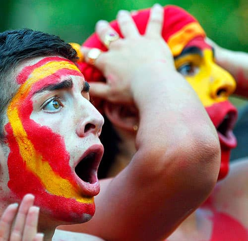 Spain soccer fans with painted faces reacting to a World Cup match.
