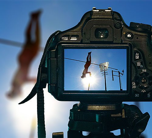 A professional camera on a tripod captures a high jump performance