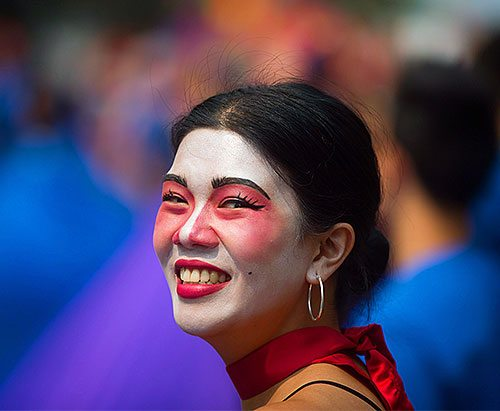 Photo of a smiling woman with theater make-up on.