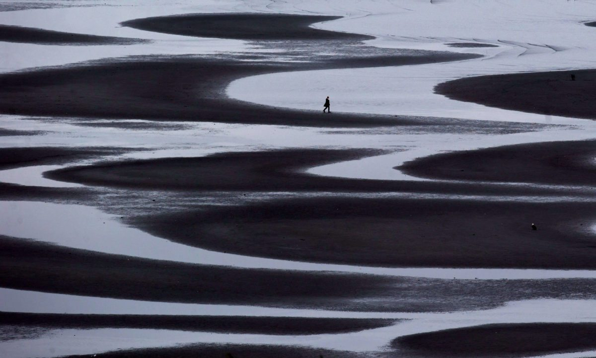 A woman walking through a tidal pool along the shore of Semiahmoo Bay during low tide in White Rock, British Columbia.