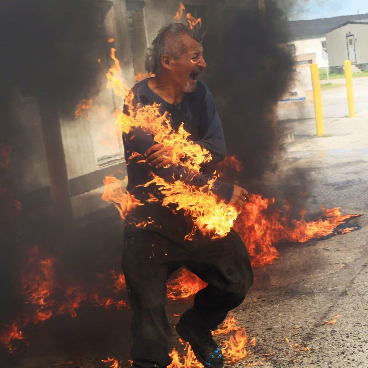 Protester engulfed in flames after attempting to pour gas on a fire..