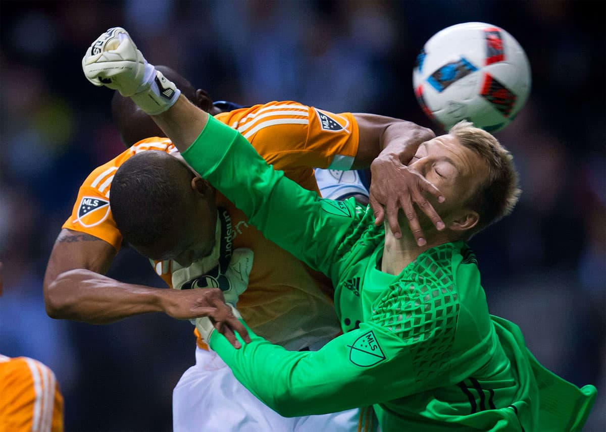 Dynamo's Ricardo Clark gets his hand in the face of teammate, goalkeeper Joe Willis, as he tries to punch the ball away from Vancouver Whitecaps' Kekuta Manneh.