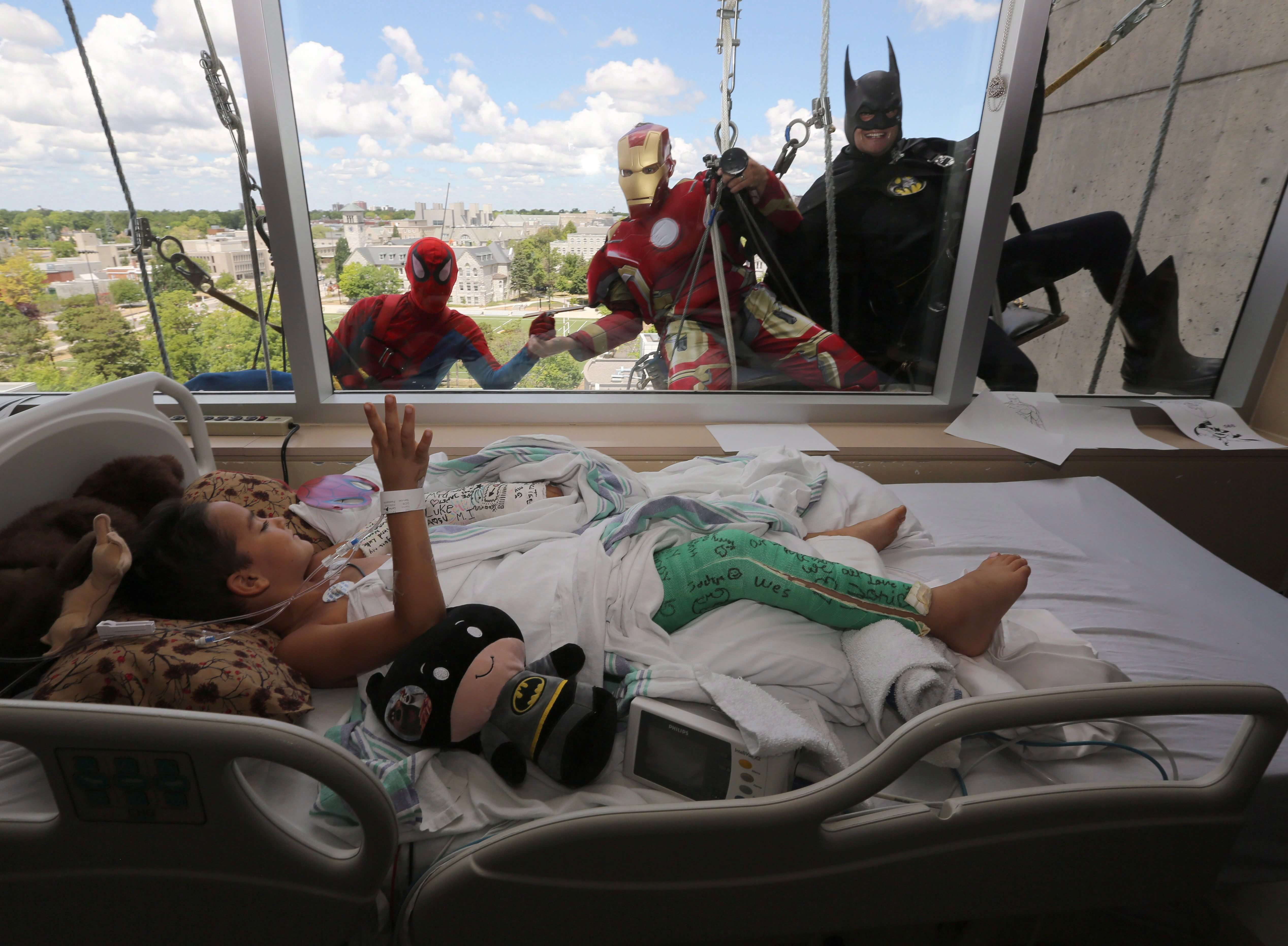 Seven-year-old Luke Carter waves to window washers dressed as Spiderman, Ironman and Batman at Kingston General Hospital in Kingston, Ontario.