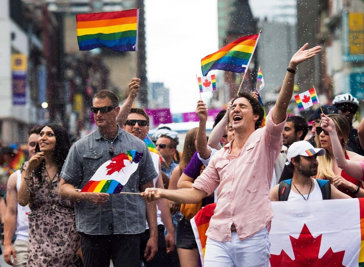Prime Minister Justin Trudeau gets splashed with water as he waves a flag while taking part in the annual Pride Parade in Toronto.