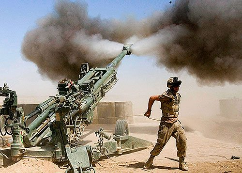 Cannon being fired by soldiers in a desert.