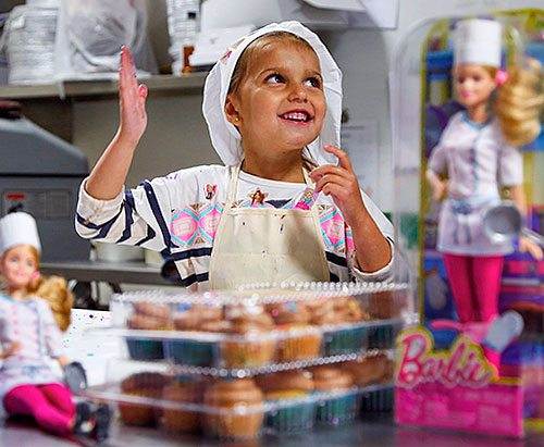 Little girl dressed like a baker surrounded by Barbie dolls in a baker outfit.
