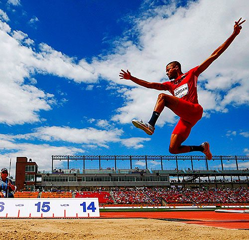 Athlete pictured in midair doing the long jump.