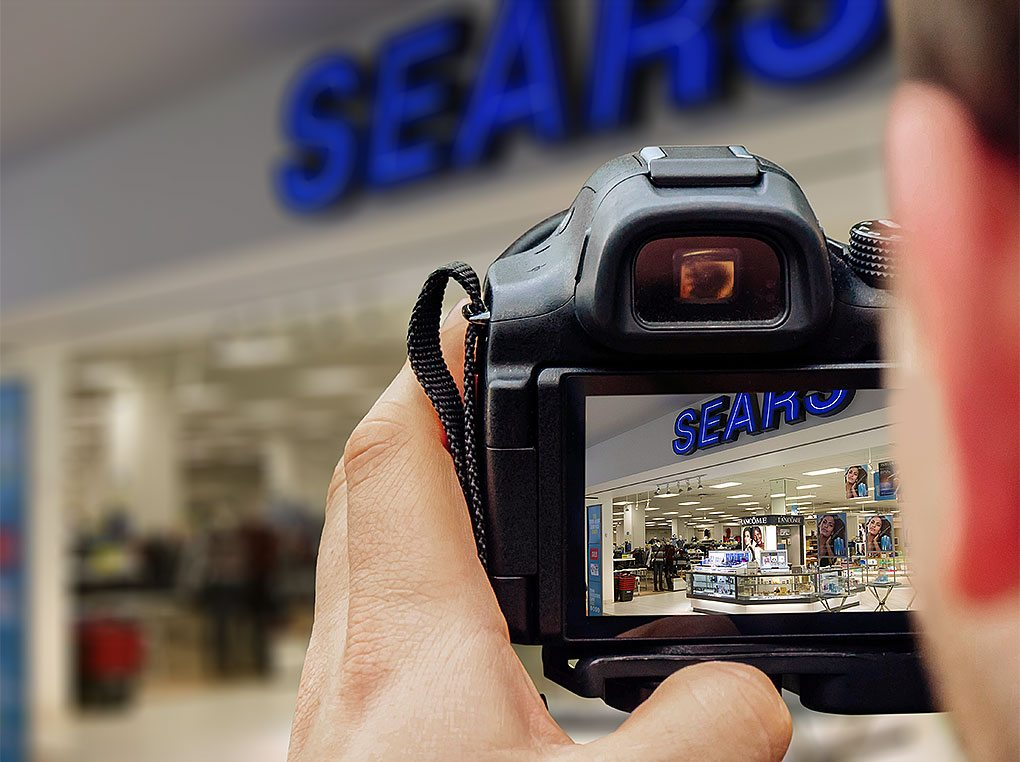A photographer captures a department storefront