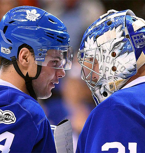 Toronto Maple Leafs teammates talking to each other on the ice.
